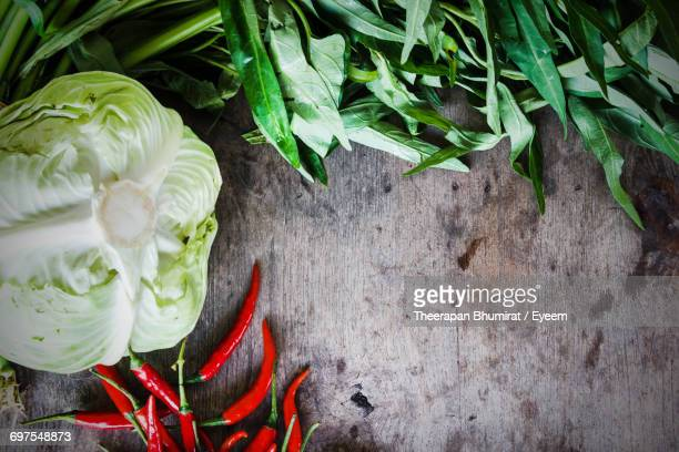 Directly Above Shot Of Leaf Vegetable With Cabbage And Chili Peppers On Wooden Table