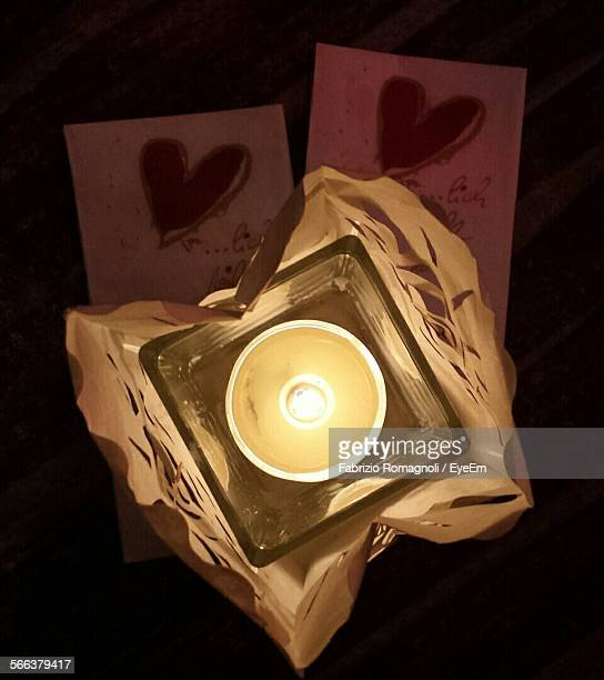 Directly Above Shot Of Lit Tea Light Candle In Container At Home