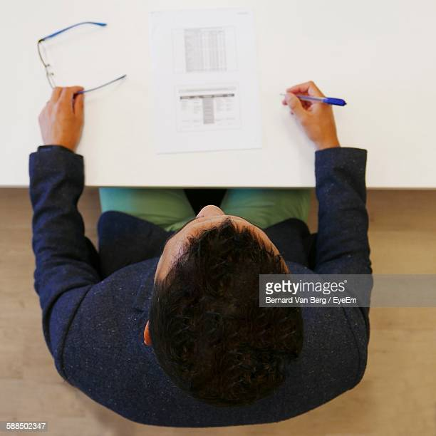 Directly Above Shot Of Man Pen And Document Sitting In Front Of Desk