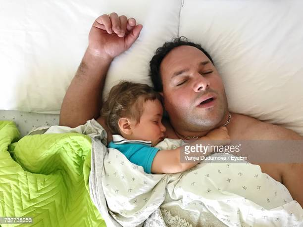 Directly Above Shot Of Man Sleeping With Baby Boy On Bed At Home