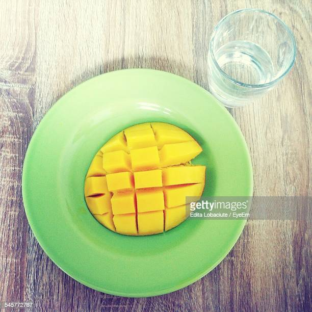 Directly Above Shot Of Mango Cubes In Plate And Glass On Wooden Table