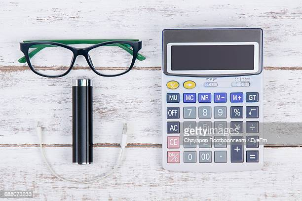 Directly Above Shot Of Mobile Phone Charger With Eyeglasses And Stationary On White Table