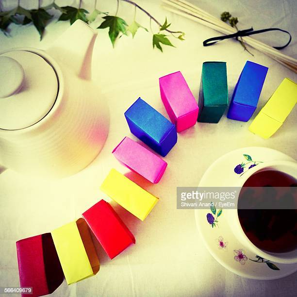 Directly Above Shot Of Multi Colored Boxes Arranged Between Teapot And Cup