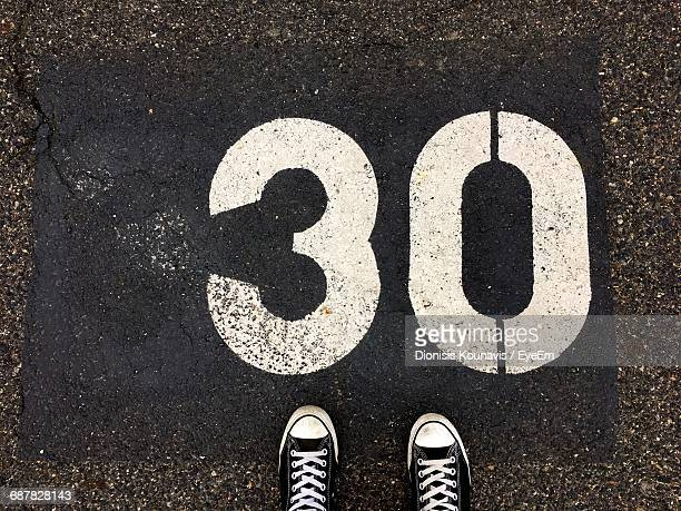 Directly Above Shot Of Number 30 By Canvas Shoe On Road