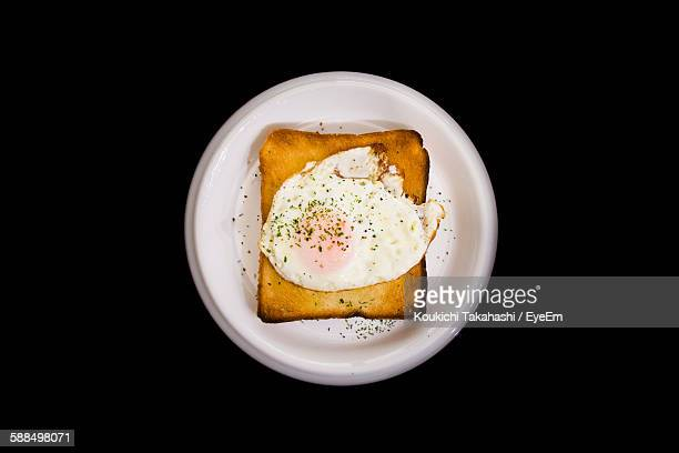 Directly Above Shot Of Omelet With Toasted Bread On Plate Against Black Background