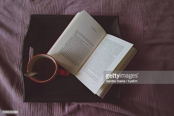 Directly Above Shot Of Open Book By Black Coffee In Cup On Tray At Bed