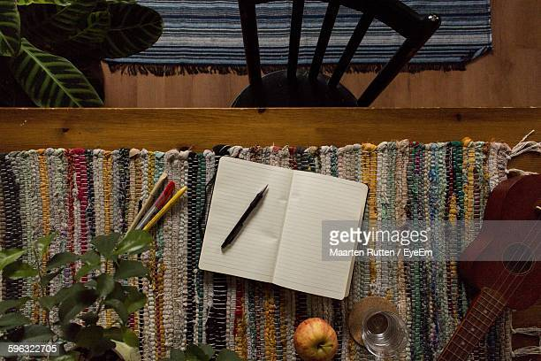 Directly Above Shot Of Open Book With Apple And Ukulele On Table