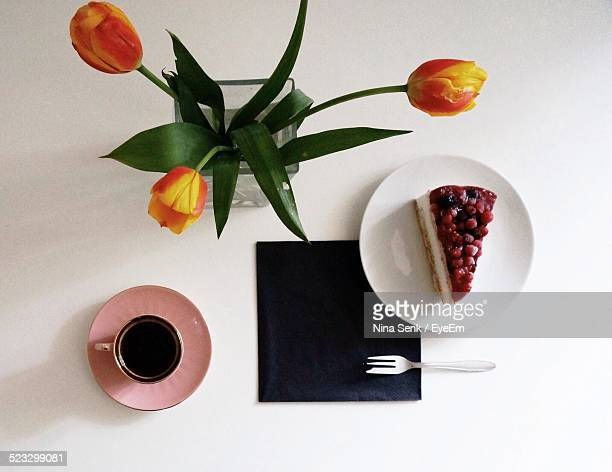 Directly Above Shot Of Pastry And Coffee With Flower Vase On White Table
