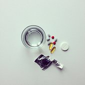 Directly Above Shot Of Pills With Drinking Glass And Package On White Table