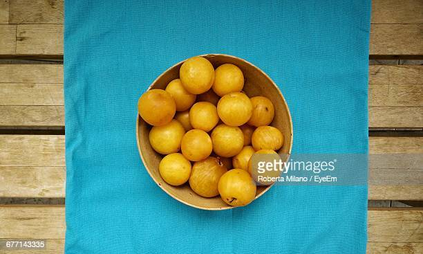 Directly Above Shot Of Plums In Bowl On Table At Kitchen
