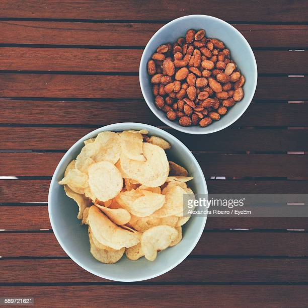 Directly Above Shot Of Potato Chips And Peanuts In Bowl On Wooden Table