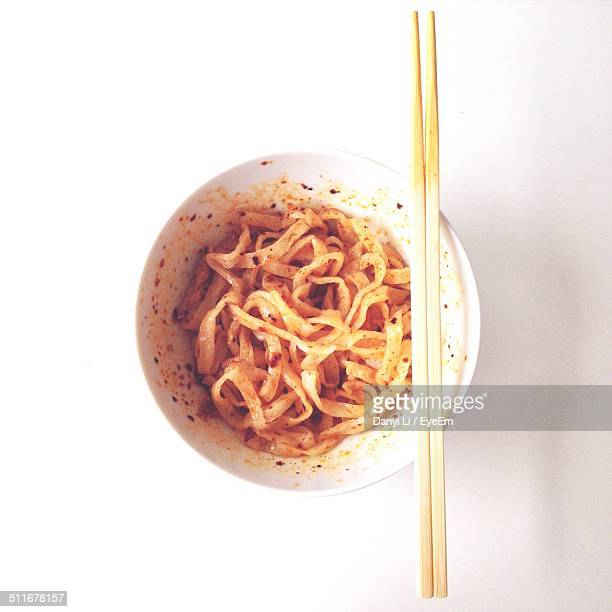 Directly above shot of prepared noodles in cup against white background