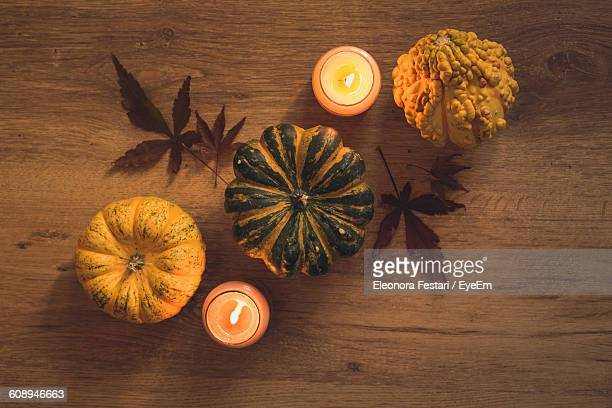 Directly Above Shot Of Pumpkins By Lit Candles On Wooden Table