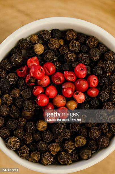 Directly Above Shot Of Ripe And Dry Black Peppercorns In Bowl On Table