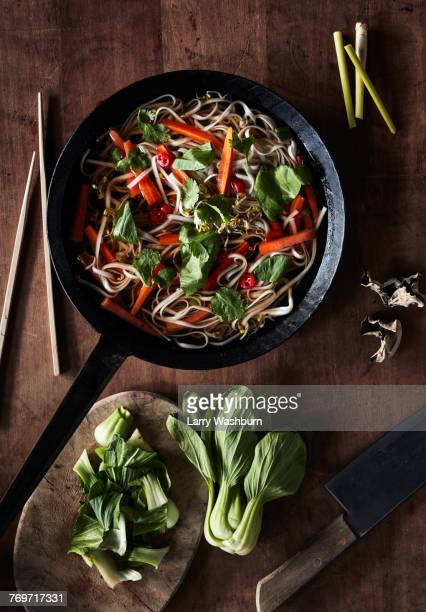 Directly above shot of salad served in saucepan with knife on table
