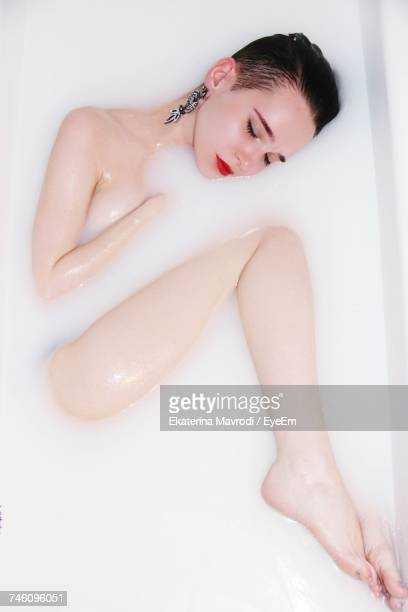 Directly Above Shot Of Sensuous Woman With Eyes Closed In Bathtub