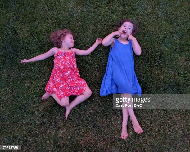 Directly Above Shot Of Siblings Lying Down On Grassy Field