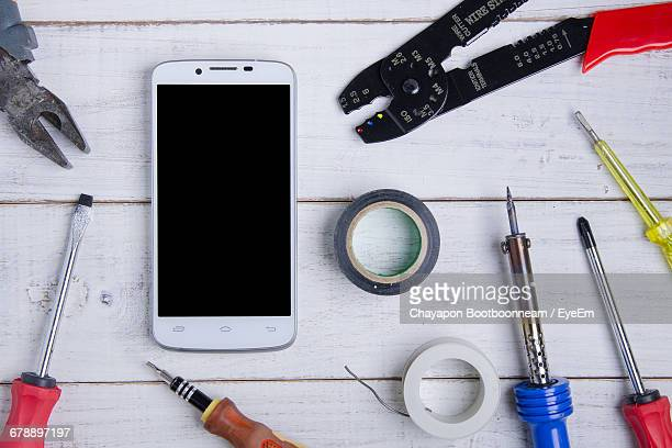 Directly Above Shot Of Smart Phone With Mechanic Tools On Table