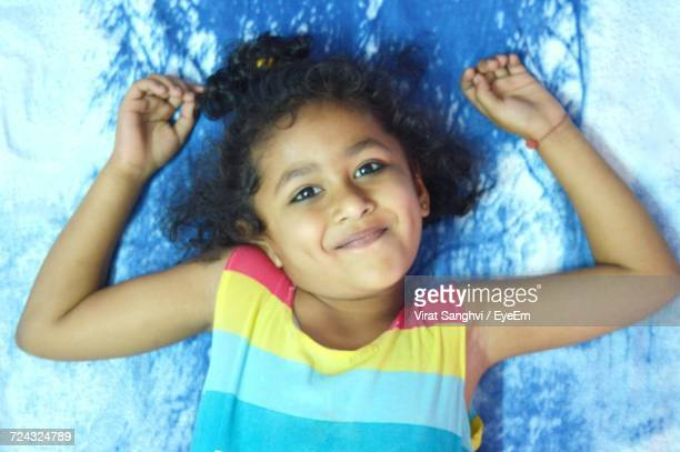 Directly Above Shot Of Smiling Girl Lying On Bed At Home