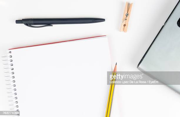 Directly Above Shot Of Spiral Notebook And Office Supply On White Background
