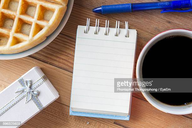 Directly Above Shot Of Spiral Notebook With Black Coffee And Waffle By Gift On Table