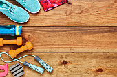 Directly above flat lay shot of sports equipment on hardwood floor. Sports shoes are placed with water bottle  dumbbells  leggings and jump rope on wood. All are representing healthy lifestyle.