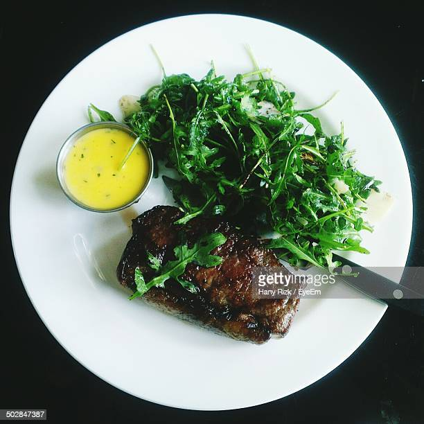 Directly above shot of steak with rucola salad and mayonnaise on plate