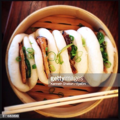 Directly above shot of steamed pork buns served in wooden container