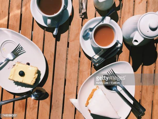 Directly Above Shot Of Tea Cups And Cakes In Plates On Table At Cafe