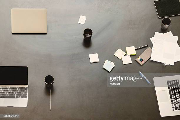 Directly above shot of technologies with coffee mugs and adhesive notes on table
