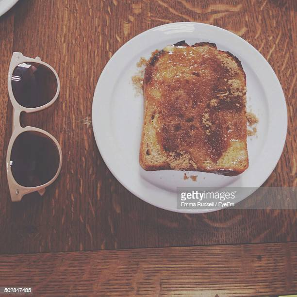 Directly above shot of toast in plate by sunglasses on wooden table