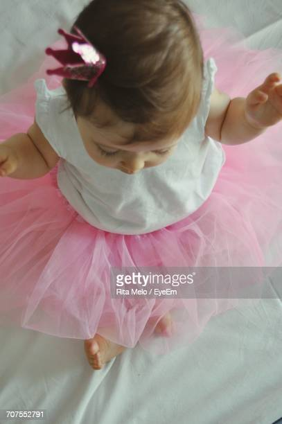 Directly Above Shot Of Toddler Baby Girl Wearing Pink Dress With Crown