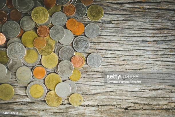 Directly Above Shot Of Various Coins On Wooden Table