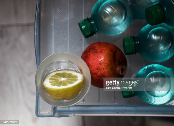 Directly Above Shot Of Water Bottles With Pomegranate And Lemon In Tray
