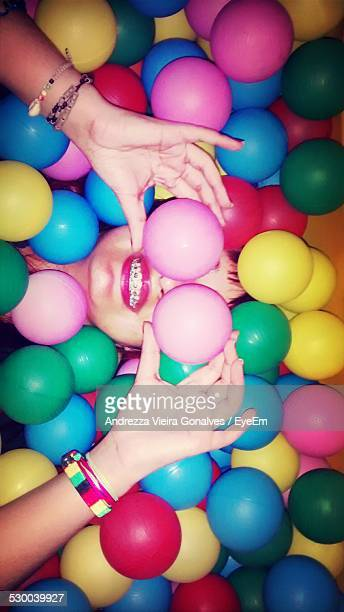 Directly Above Shot Of Woman Covering Eyes With Pink Balls While Lying Amidst Them