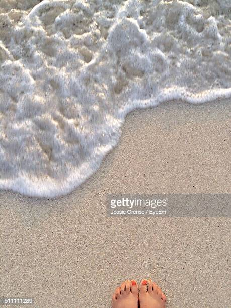 Directly above shot of woman feet by surf at beach