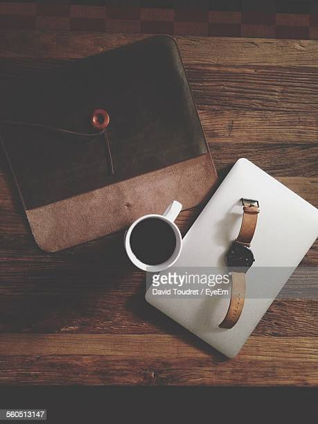 Directly Above Shot Of Wristwatch On Mobile Phone With Wallet On Table