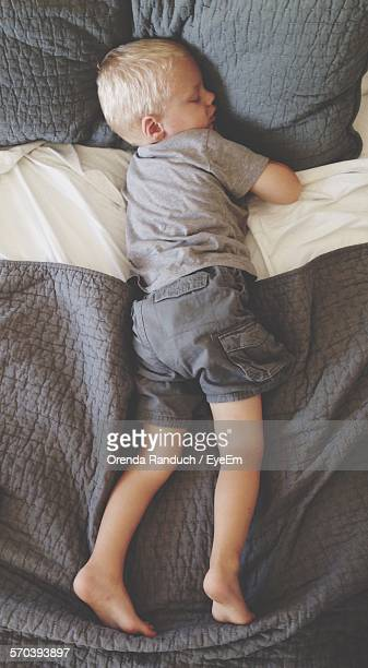 Directly Above View Of Boy Sleeping On Bed At House