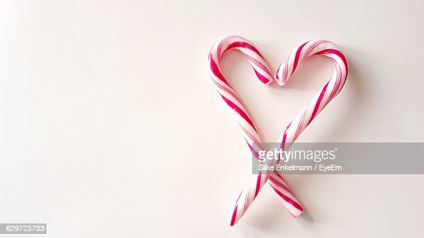 Directly Above View Of Candy Canes In Heart Shape On White Background