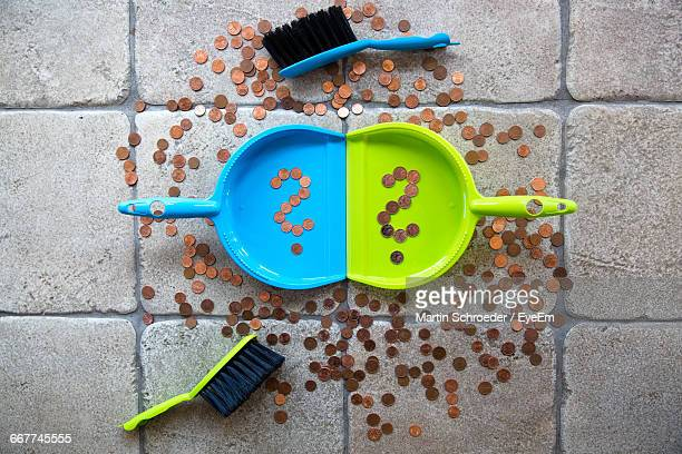 Directly Above View Of Coins In Dustpan And Scattered Flooring