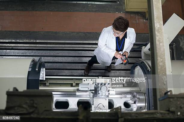 Directly above view of female worker operating machine