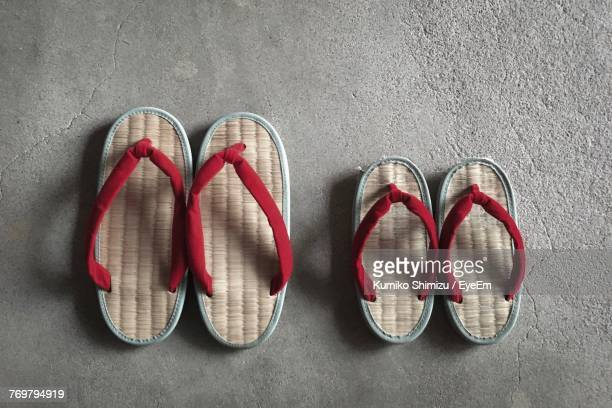 Directly Above View Of Flip-Flops On Concrete Floor