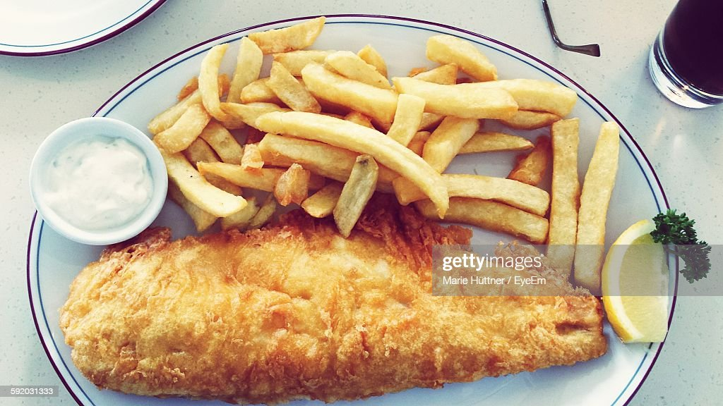 Directly Above View Of French Fries And Fried Fish Served In Plate On Table