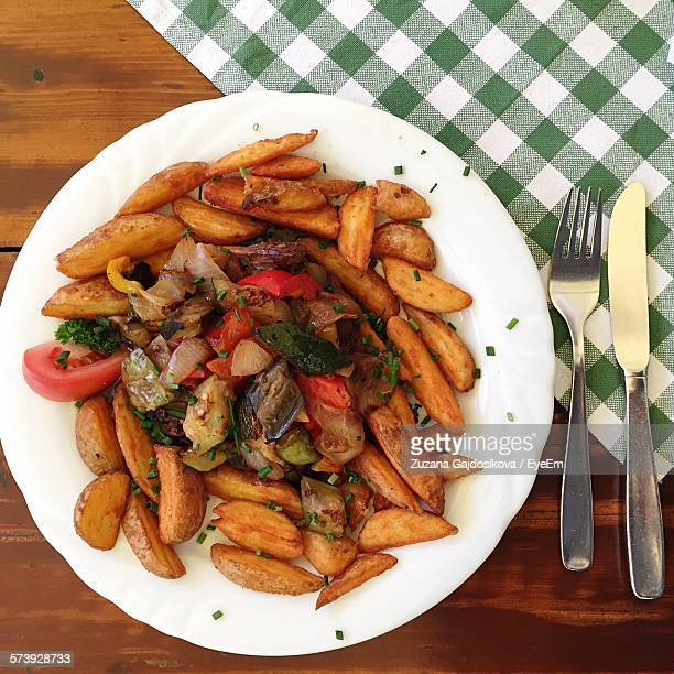 Directly Above View Of Fried Potato Wedges In Plate With Vegetable At Restaurant