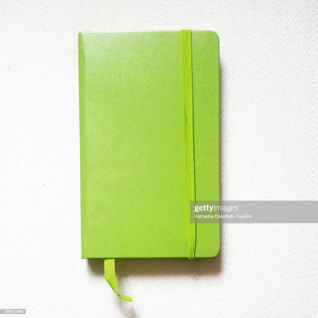 Directly Above View Of Green Diary Over White Background