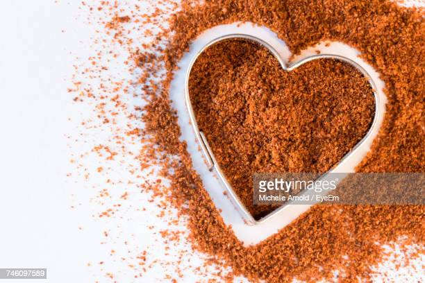 Directly Above View Of Grounded Cayenne In Heart Shaped Container
