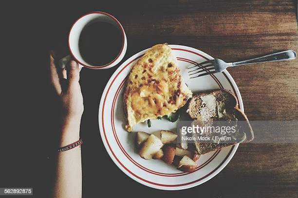 Directly Above View Of Hand Holding Coffee Cup With Breakfast Plate On Table