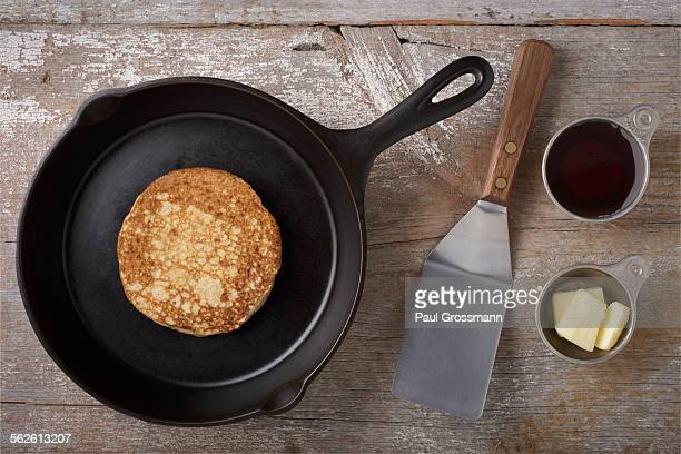 Directly above view of kitchen utensils and pancake on rustic wooden table