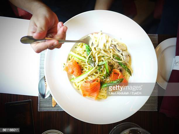 Directly Above View Of Man Eating Salmon Pasta In Impiana Hotel