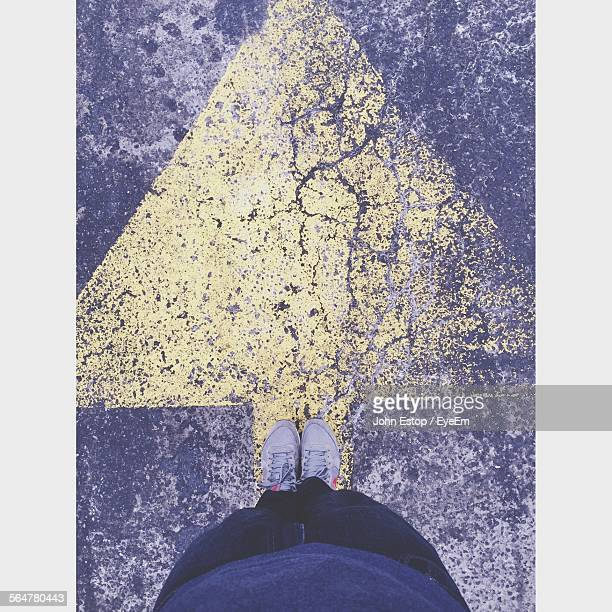 Directly Above View Of Man Standing On Road Arrow Sign